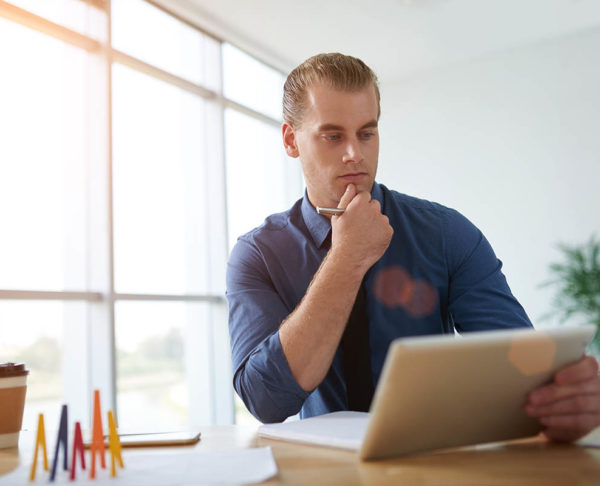Pensive young entrepreneur reading e-mails on digital tablet