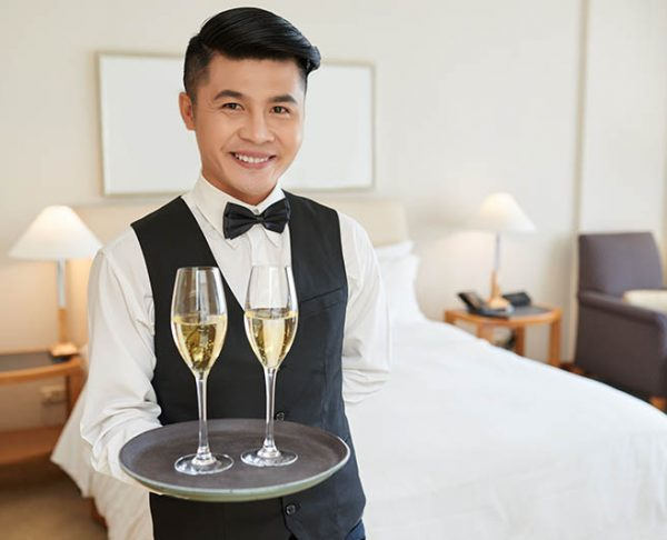 Smiling handsome waiter with two glasses of champagne